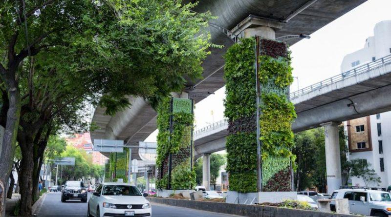 Ambiente urbano con giardini verticali intorno a una strada e con delle macchine di passaggio