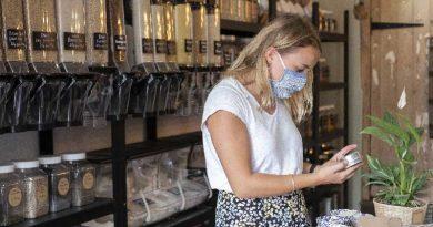 Donna bionda che scegli cibo sostenibile da un negozio